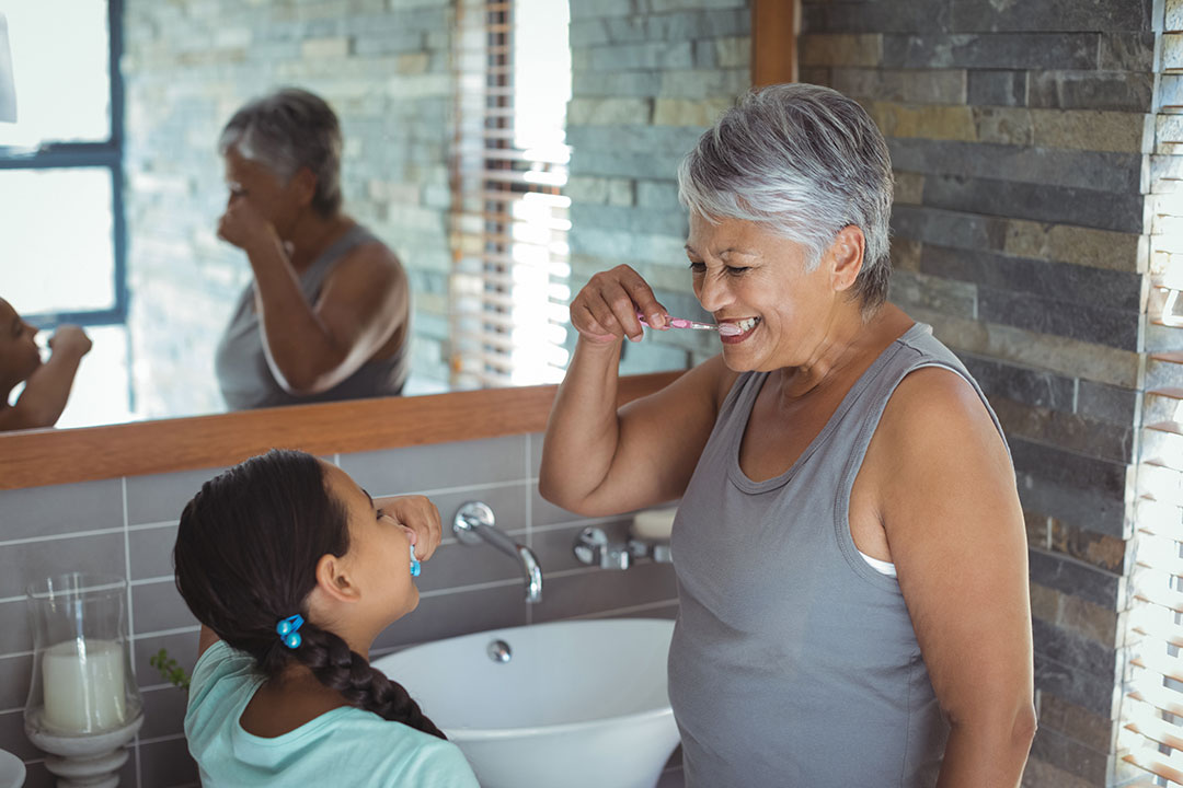 Grandmother and Granddaughter Brushing Teeth Together