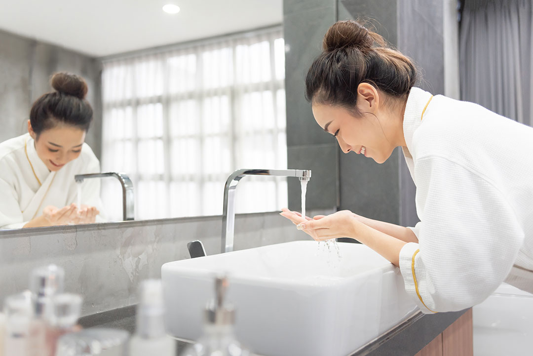 Asian Girl in White Robe Washing Hands in Bathroom Sink